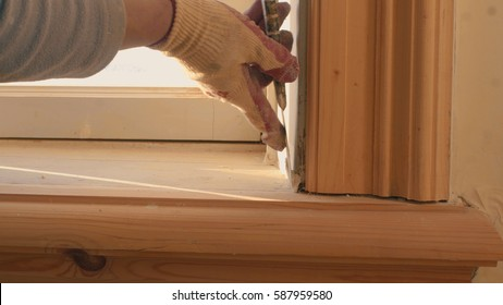 Man's hand puttied wooden frame of the window. Close up.