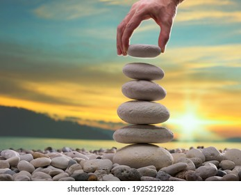The man's hand is putting gravel on the stone tower. Personal Development Concept