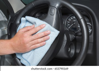 Man's hand with rag cleaning a car steering wheel. Early spring cleaning or regular clean up.
