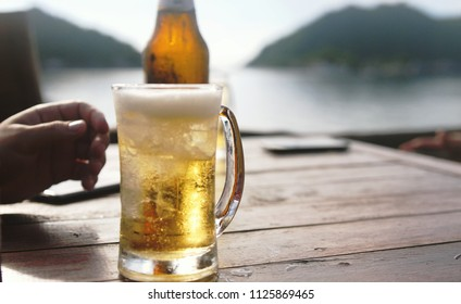 Man's hand reaches for a glass of beer in a beach cafe. Vacation theme concept