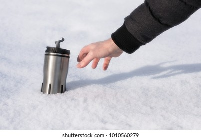 A man's hand reaches for a thermos with hot coffee in the snow