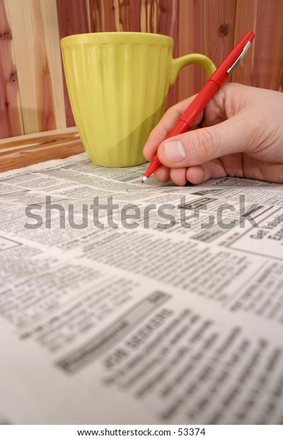Man's hand with red pen making circles in the want ads (or personals). Yellow mug of coffee behind his hand.