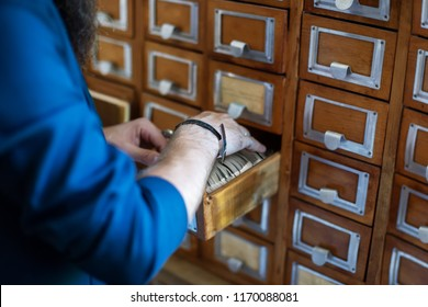Man's hand searching for files into library or archive reference card catalog, close up