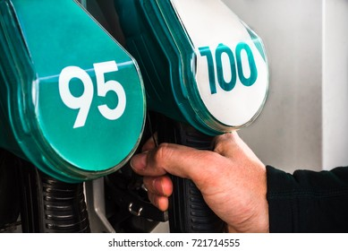 Mans hand selects 100 or 95 octane number (European RON rating) out of quality gasoline nozzle guns at petrol station refuelling stand - automotive business or environmental pollution closeup backdrop