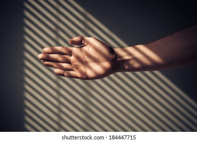 Man's hand with shadows being cast from blinds