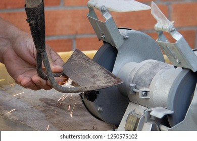 mans hand sharpens a hoe on electric grindstone in rural shed.