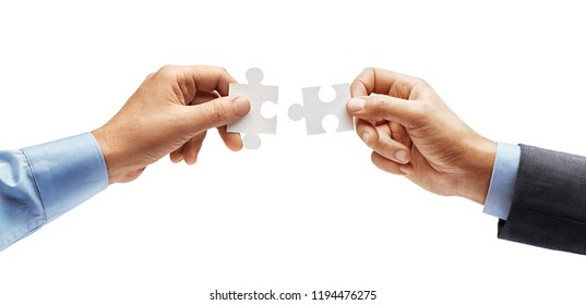 Man's hand in shirt and man's hand in suit trying to connect puzzle pieces isolated on white background. Close up. High resolution product