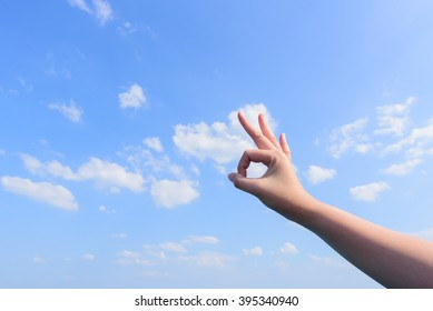 Man's hand showing an Okay sign blue sky and clouds background