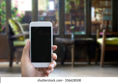 Man's hand shows mobile smartphone in vertical position, blurred background - mockup template