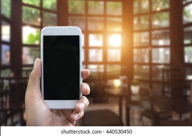 Man's hand shows mobile smartphone in vertical position and blurred background