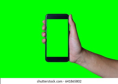Man's hand shows mobile smartphone with green screen in vertical position isolated on green background - mockup template and clipping path