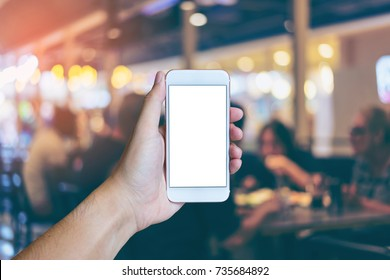 Man's hand shows mobile smartphone with white screen in vertical position,  Blurred or Defocus image of Restaurant or Cafeteria for use as Background vintage tone. - mockup template and clipping path