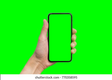 Man's hand shows mobile smartphone with green screen in vertical position isolated on green background. Mock up mobile