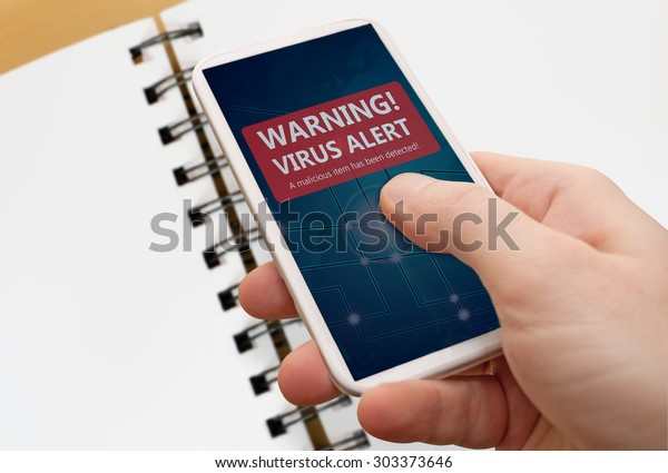 Man's Hand With Smartphone With Virus Alert Warning Sign on Display - Notebook in Background