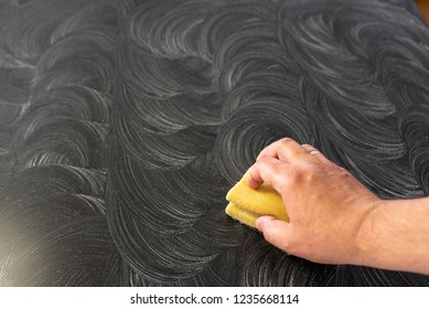 mans hand with a sponge and abrasive cleaner, cleaning black granite kitchen top, white spiral lines from the abrasive, top view