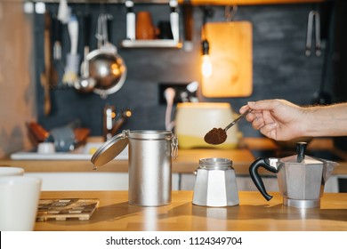 Mans hand with a spoon of ground coffee is filled with a geyser retro coffee maker on a wooden table.