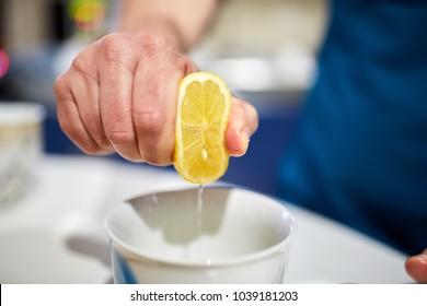 Man's hand squeezing half a lemon into a bowl