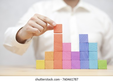 Man's hand stacking colorful wooden blocks. Business development concept