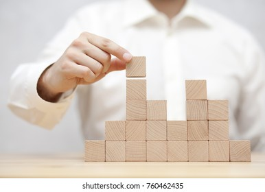 Man's hand stacking wooden blocks. Business development concept