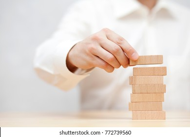 Man's hand stacking wooden blocks. Business development concept.