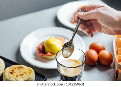 Man's hand stirring coffee in a glass shot against served breakfast