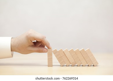 Man's hand stopping the domino effect. Concept image for business strategy and crisis solution.