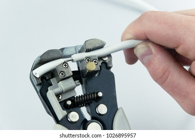 The man's hand strips the wire.Close-up