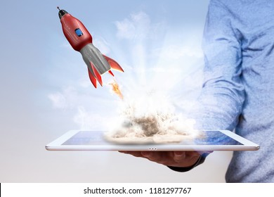 Mans hand with tablet pc and flying rocket.