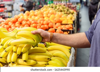 mans hand take bananas from shelf of store. healthy food. shopping concept.