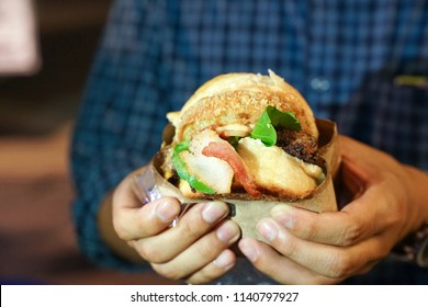 man's hand take big hamburger / bacon, hold and ready to bite it in his mouth, at Thailand foodtruck event.