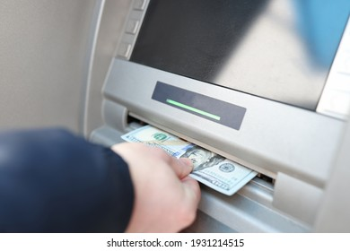 Man's hand takes out banknotes from an ATM. Bank customer service concept