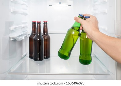 A man's hand takes two glass bottles of beer from the refrigerator. close-up
