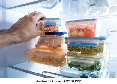Man's Hand Taking Container Of Frozen Mixed Vegetables From Refrigerator