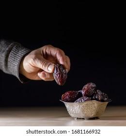 Die Hand des Menschen nimmt die Dattelfrucht aus der schönen Schüssel zur rechten Zeit, symbolisiert Ramadan