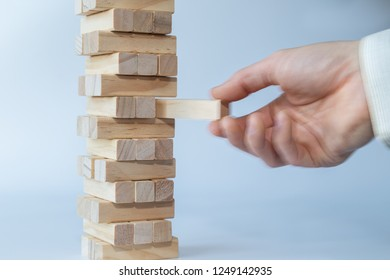 Man's hand taking the first block or putting the last block to a sturdy tower of wooden blocks. Concept photo of planning, taking risks and strategizing. Hand is in motion. Light gray background.