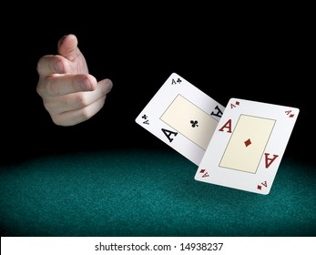 A man's hand throwing two aces over a green felt.