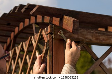 The man's hand tightens the screw with a wrench. Renovation and maintenance and repair of wooden garden furniture.