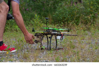 Man's hand is touching the drone with green props. Man is in red sneakers. Summer. Drone stand on grass in front of the forest.