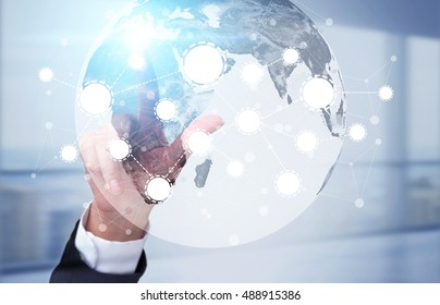 Man's hand touching a screen with globe and startup icons. Concept of international trade.Toned image. Double exposure