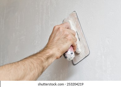 Man's hand with trowel plastering an interior wall. Selective focus.