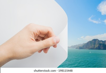 Mans hand turning the page revealing a coastal scene