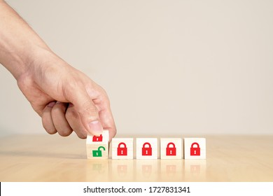Man's hand turning wooden box red key lock to green unlock key. Start unlock lockdown after coronavirus covid-19 pandemic or epicdemic crisis. Time to reopening, relunch or restart concept