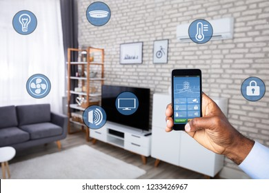 Man's Hand Using Home Control System On Cellphone With Various Icons