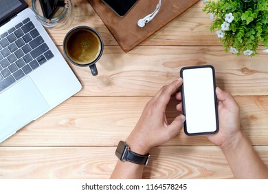 Man's hand using mobile smartphone on wooden desk and office supplies, Blank screen mobile phone for graphic display montage.