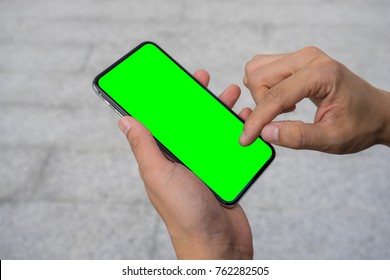 Man's hand using mobile smartphone with green screen. Mock up mobile