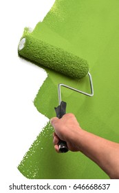 Man's hand using paint roller on white wall