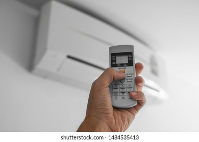 Man's hand using remote controler. Hand holding rc and adjusting temperature of air conditioner mounted on a white wall. Indooor comfort temperature. Health concepts and energy savings.