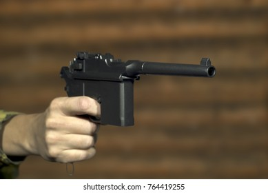 A man's hand with a vintage semi-automatic pistol points past the frame on the background of a log wall. Focus on the muzzle of the pistol, the rest is blurry.