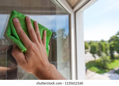 A man's hand washes the window with a green rag