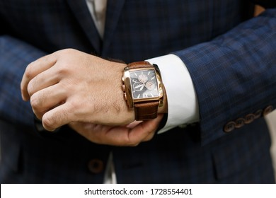A man's hand with a watch. Businessman. The groom fastens the watch